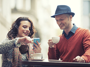 A Man with Coffee and a Woman Showing Him Checking Account Tips on Her Mobile Device