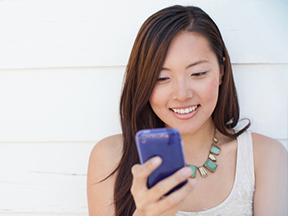 Woman looking at an online banking alert on her mobile phone