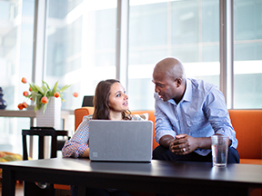 A man giving money management tips to a woman in front of a laptop
