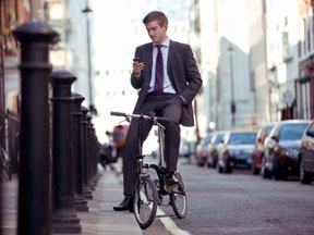 Business man on bike setting up automatic bill pay on his mobile phone